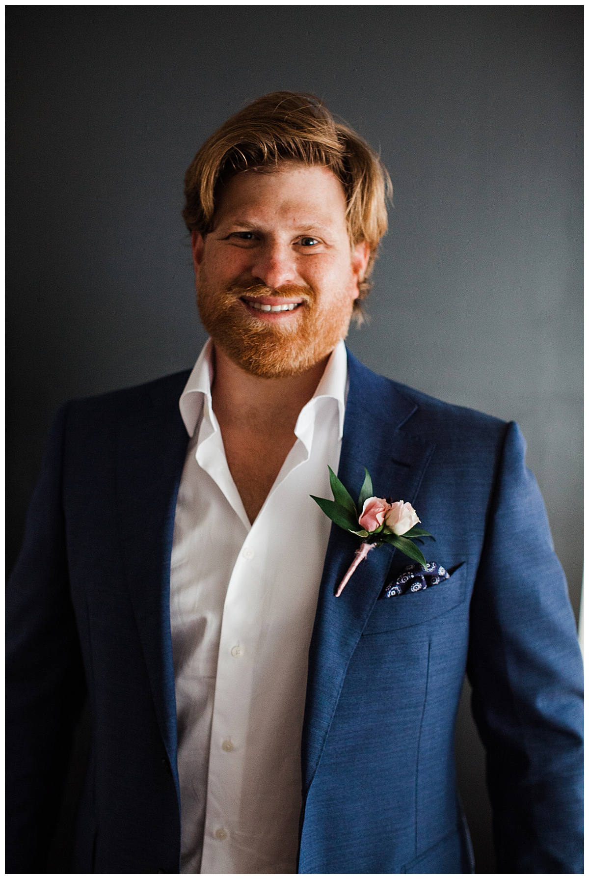 Groom smiling in blue and white suit