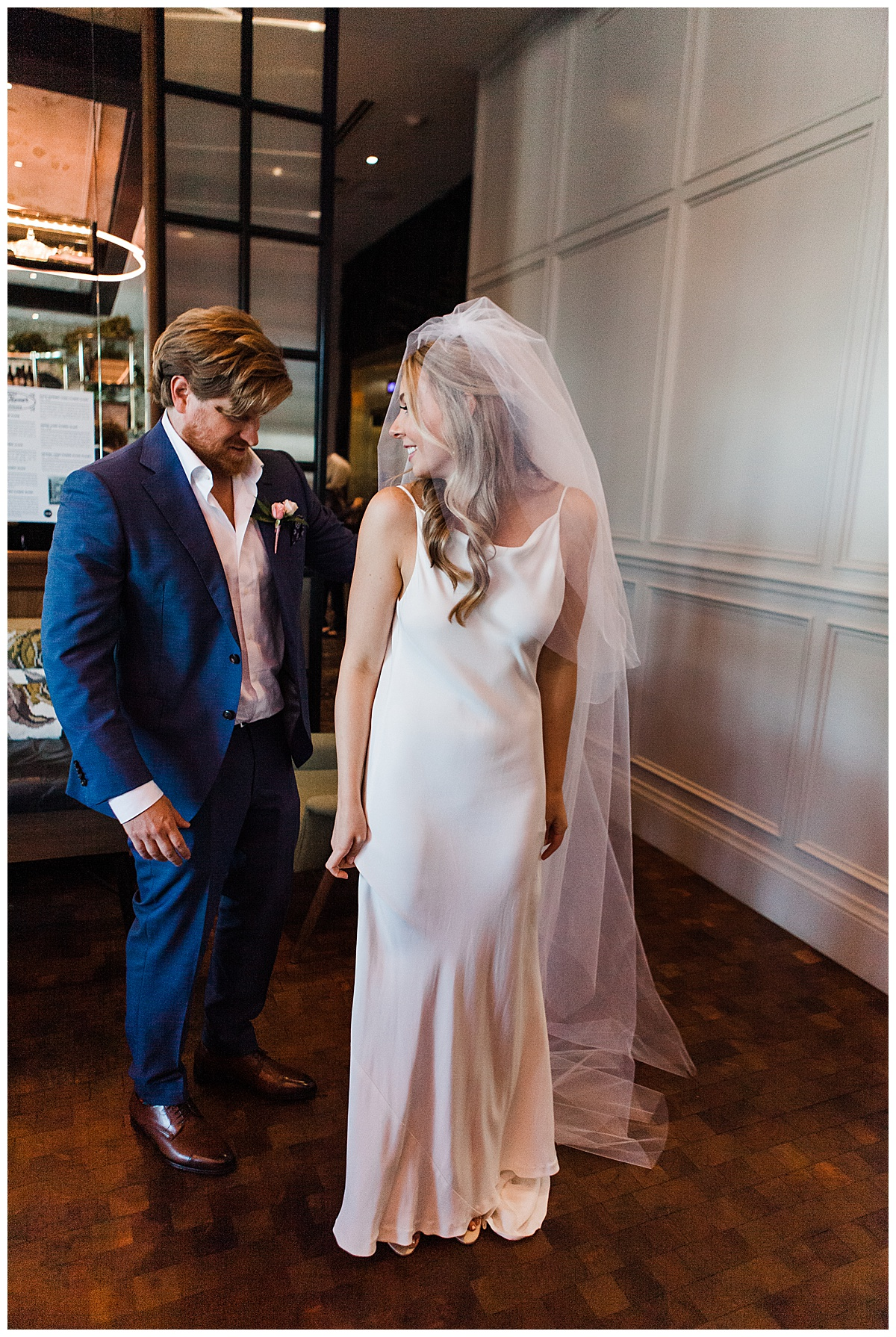 Groom looks at bride while she looks over shoulder | First look wedding