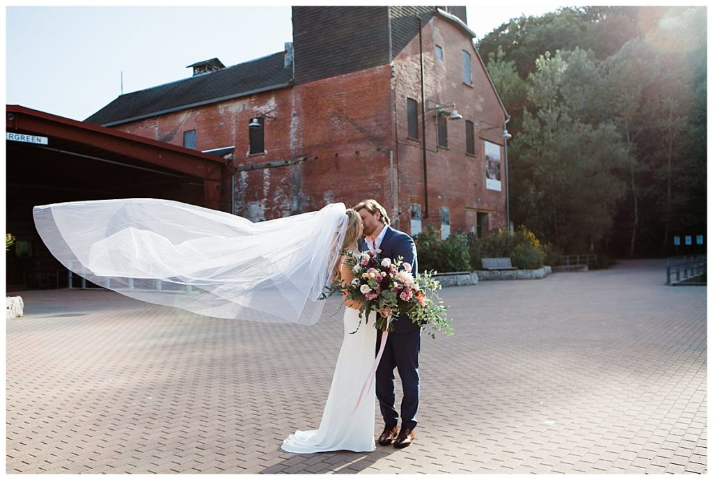 Bride and groom kiss while wedding veil flows in wind
