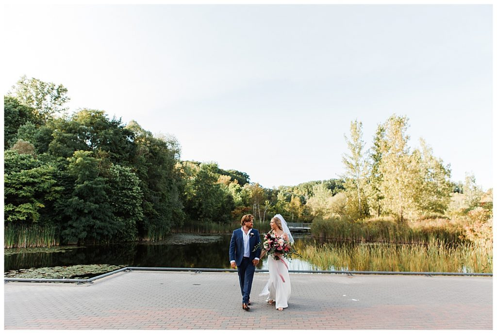 Bride and groom walking in front of lake