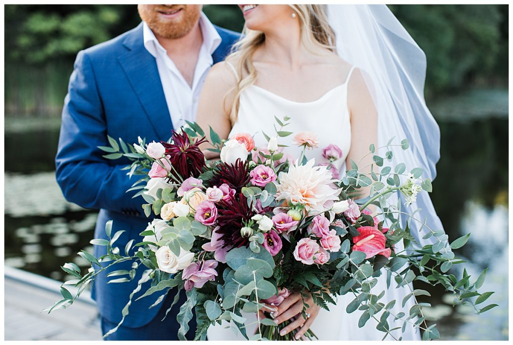 Groom and bride snuggling holding wildflower bridal bouquet