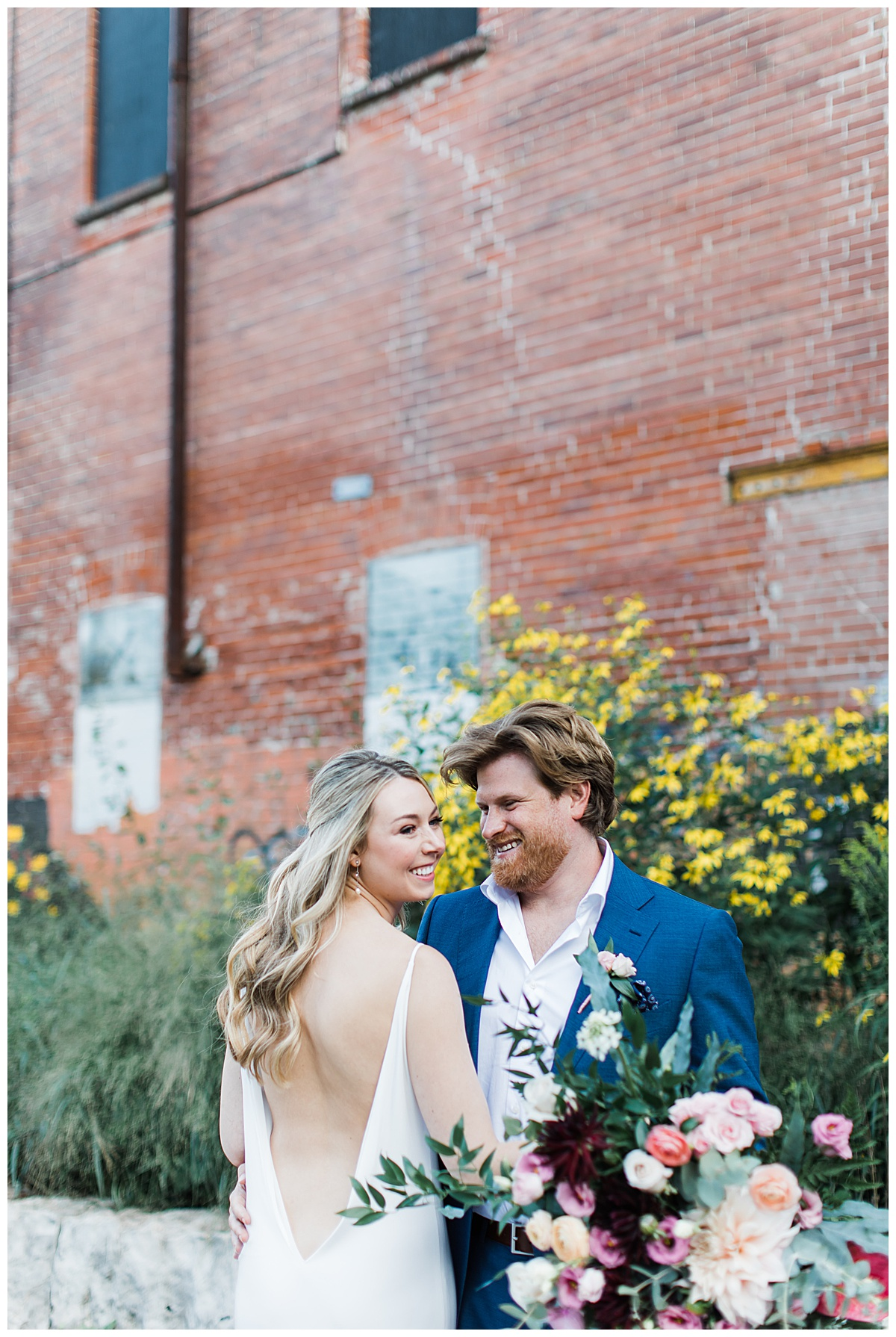 Bride in low back dress smiling with groom | wildflower wedding bouquet