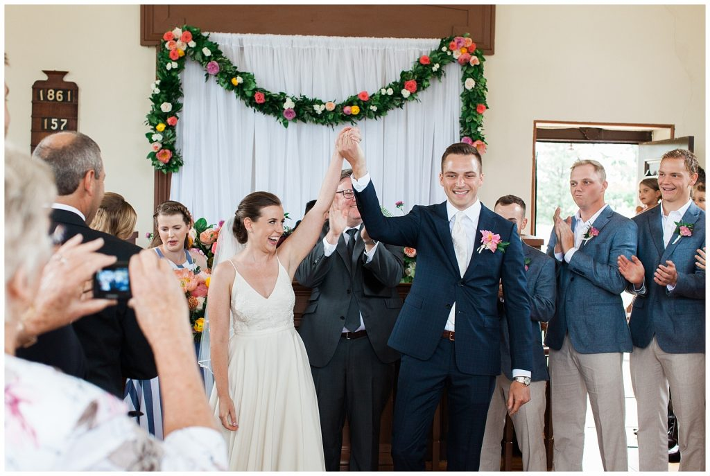 Bride and groom holding hands in the air in victory at Guelph Ontario Wedding | Ontario Wedding Photographer | Toronto Wedding Photographer | 3photography