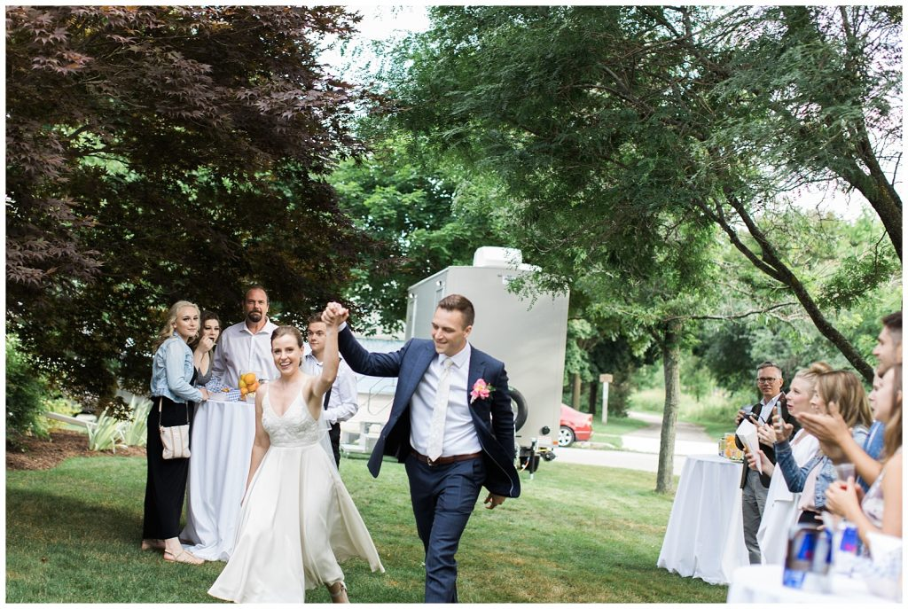 Bride and groom holding hands in the air in victorious manner after ceremony at Guelph Ontario Wedding | Ontario Wedding Photographer | Toronto Wedding Photographer | 3photography