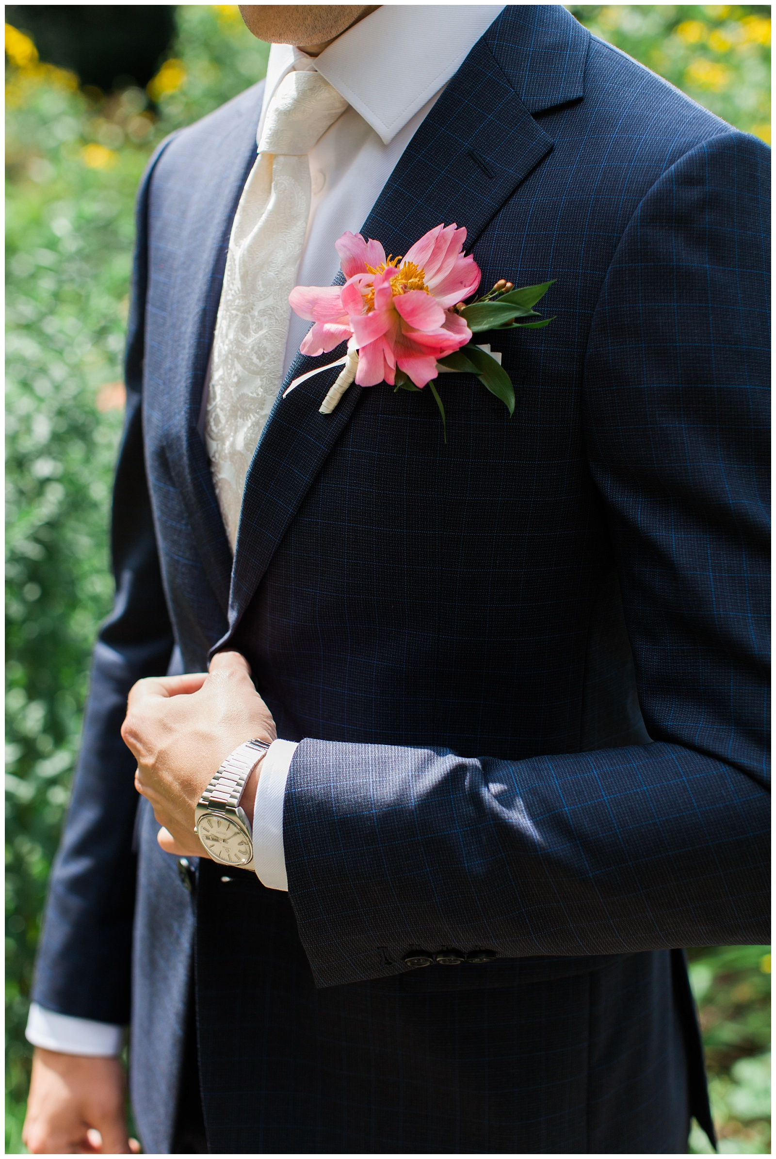Close up of groom attire Navy pinstripe suit and pink boutonniere