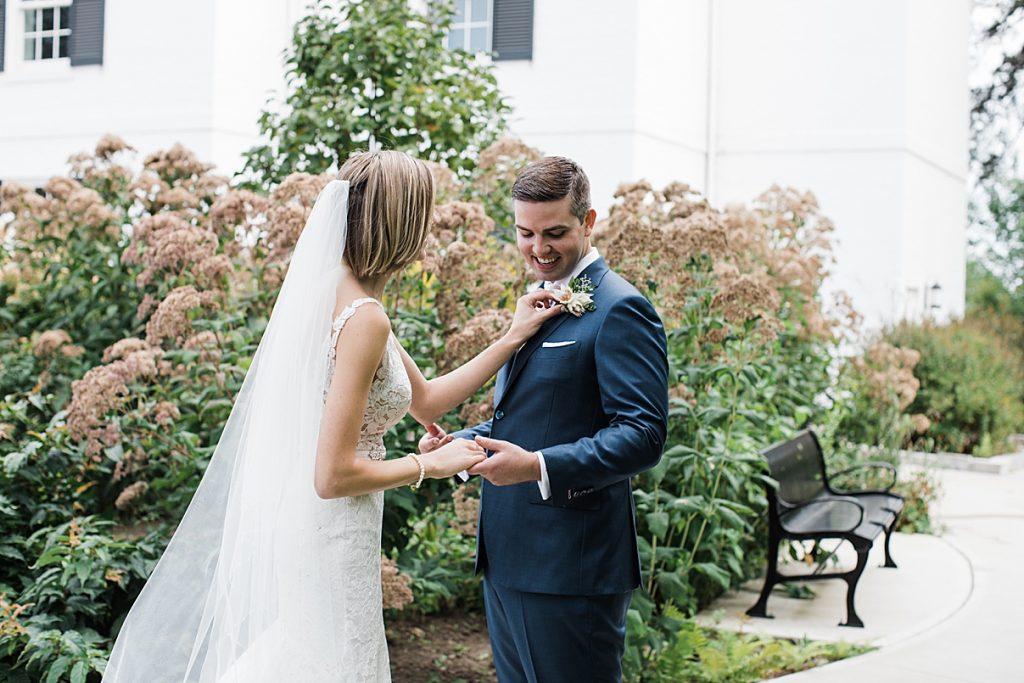 Bride adjusts groom's boutonniere| Harding Waterfront Estate Wedding| Ontario wedding photographer| Toronto wedding photographer| 3 Photography | 3photography.ca