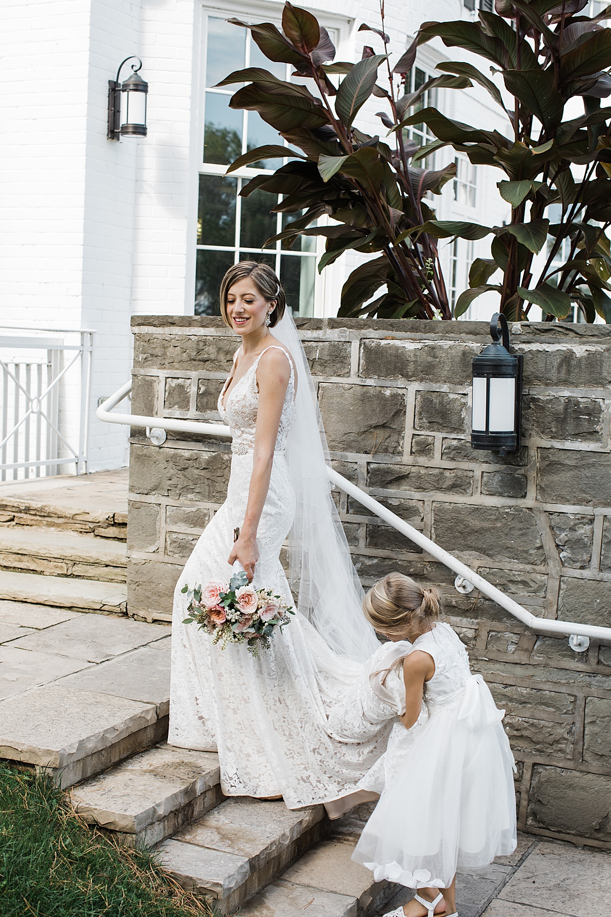 Bride walks up steps with flower girl holding her train| Harding Waterfront Estate Wedding| Ontario wedding photographer| Toronto wedding photographer| 3 Photography | 3photography.ca