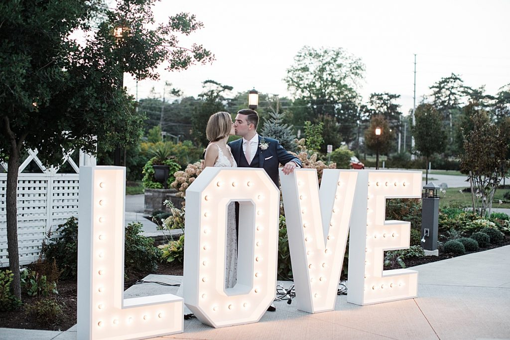 Bride and groom kiss by LOVE marquee sign| Harding Waterfront Estate Wedding| Ontario wedding photographer| Toronto wedding photographer| 3 Photography | 3photography.ca