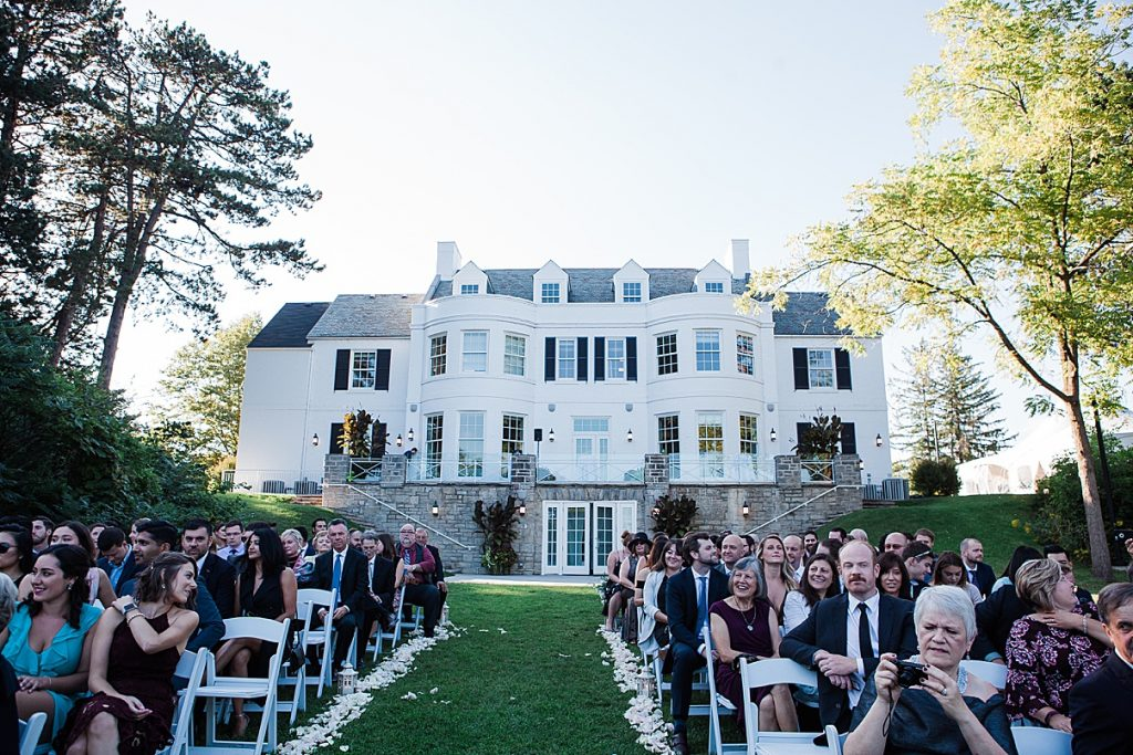 View of guests at ceremony with mansion in background| Harding Waterfront Estate Wedding| Ontario wedding photographer| Toronto wedding photographer| 3 Photography | 3photography.ca