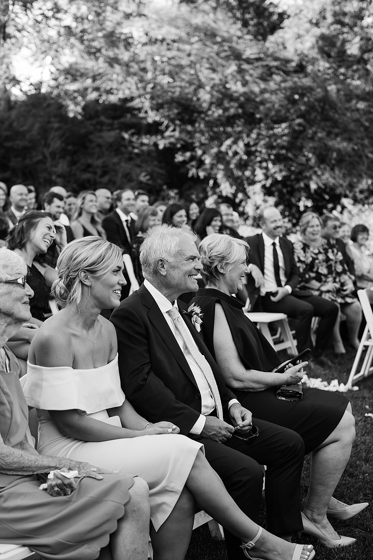 Black and white shot of guests smiling at wedding ceremony| Harding Waterfront Estate Wedding| Ontario wedding photographer| Toronto wedding photographer| 3 Photography | 3photography.ca