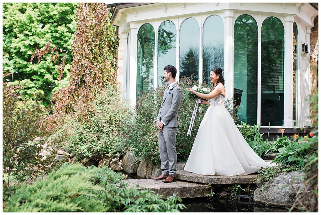 Bride taps on grooms shoulder for first look| Groom stands outside on stepping stones across tiny moat awaiting his bride| Belcroft Estate Wedding| Toronto wedding photographer| Ontario wedding photographer| 3photography