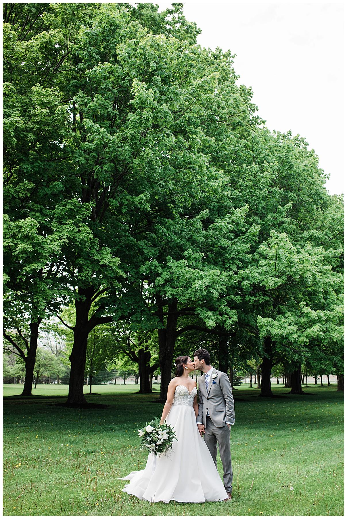 Bride and groom kiss walking across tree-farm| Belcroft Estate Wedding| Toronto wedding photographer| Ontario wedding photographer| 3photography