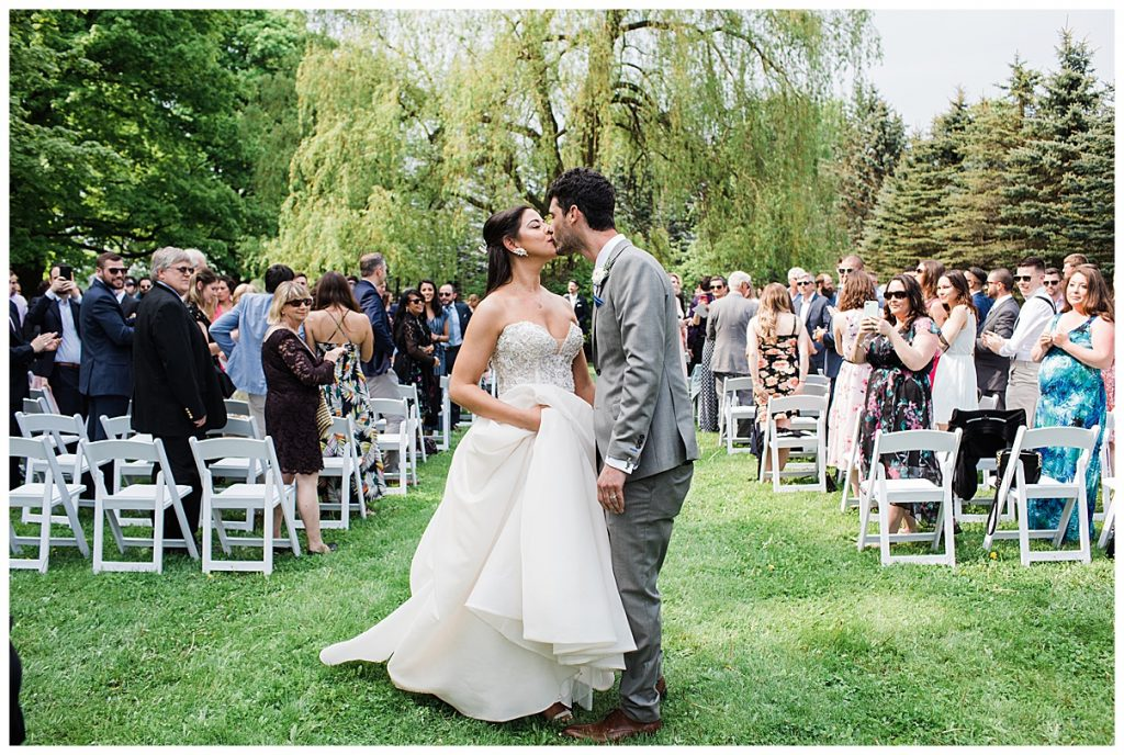 Bride and groom kiss in middle of outdoor wedding ceremony aisle| Belcroft Estate Wedding| Toronto wedding photographer| Ontario wedding photographer| 3photography