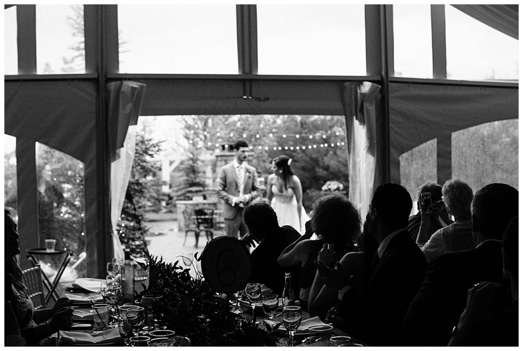 Black and white of wedding guests watching bride and groom dance under string lights| Belcroft Estate Wedding| Toronto wedding photographer| Ontario wedding photographer| 3photography