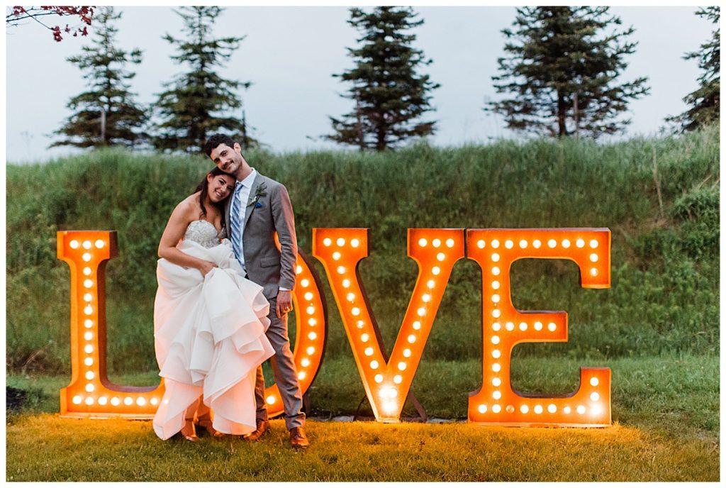 Bride lays head on groom's chest in front of LOVE marquee sign| tree-farm wedding| Belcroft Estate Wedding| Toronto wedding photographer| Ontario wedding photographer| 3photography