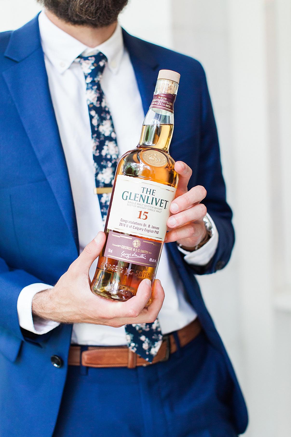 Groom showing off bottle of Scotch | Balls Falls, Ontario Wedding| Ontario Wedding Photographer| Toronto Wedding Photographer| 3Photography|3photography.ca