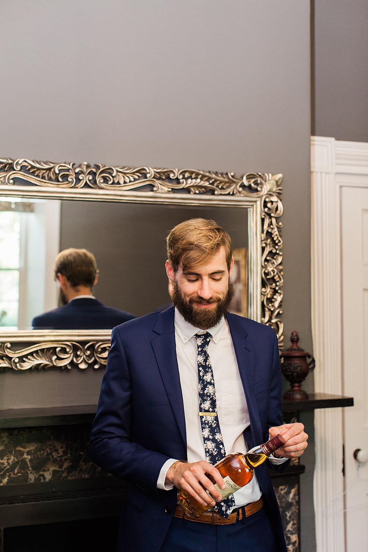 Groom standing in front of mirror opening a bottle of liquor | Balls Falls, Ontario Wedding| Ontario Wedding Photographer| Toronto Wedding Photographer| 3Photography|3photography.ca