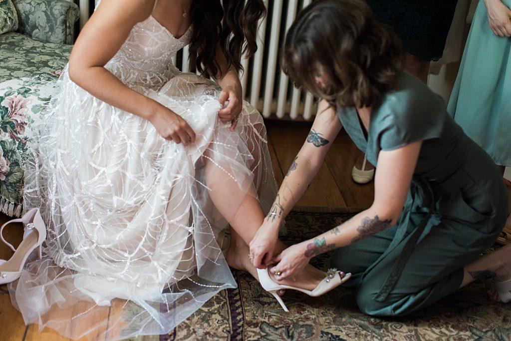 Bridesmaid helping bride put heels on | Balls Falls, Ontario Wedding| Ontario Wedding Photographer| Toronto Wedding Photographer| 3Photography|3photography.ca