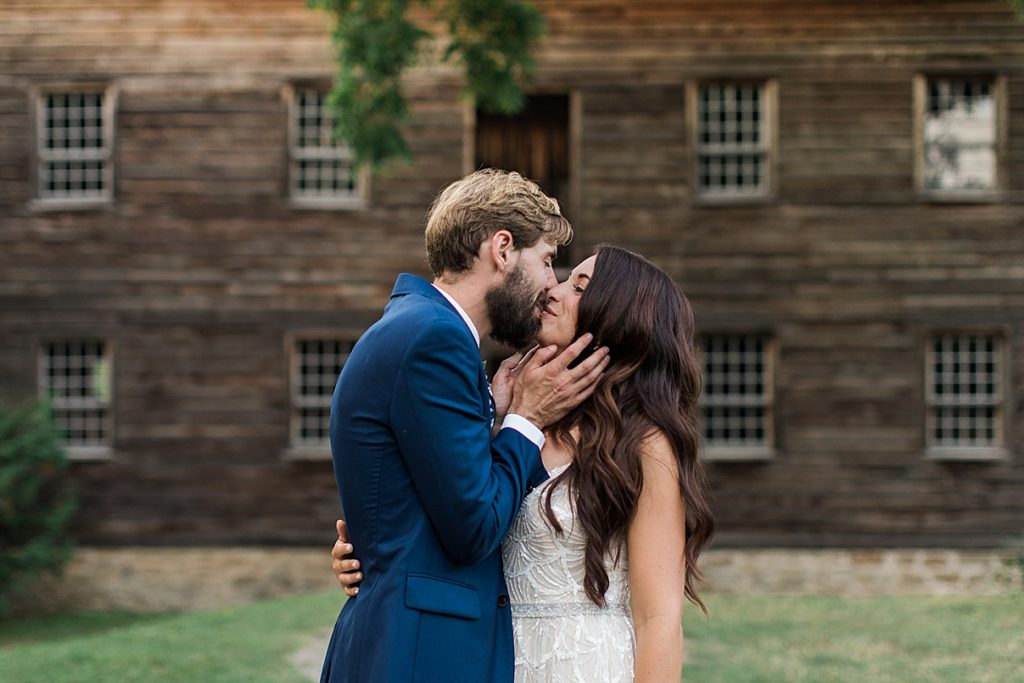 Groom and bride kiss in front of historic house   Balls Falls, Ontario Wedding  Ontario Wedding Photographer  Toronto Wedding Photographer  3Photography  3photography.ca