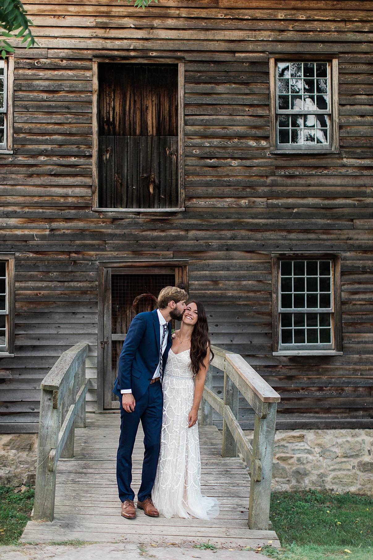 Groom smooches bride in front of abandoned house | Balls Falls, Ontario Wedding| Ontario Wedding Photographer| Toronto Wedding Photographer| 3Photography| 3photography.ca