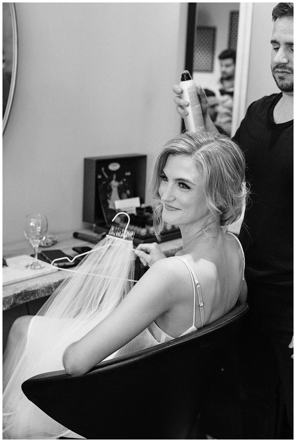 Black and white shot of bride sitting in salon chair looking back over her shoulder and grinning  Ontario Wedding  Toronto wedding photographer  Ontario wedding photographer  3photography