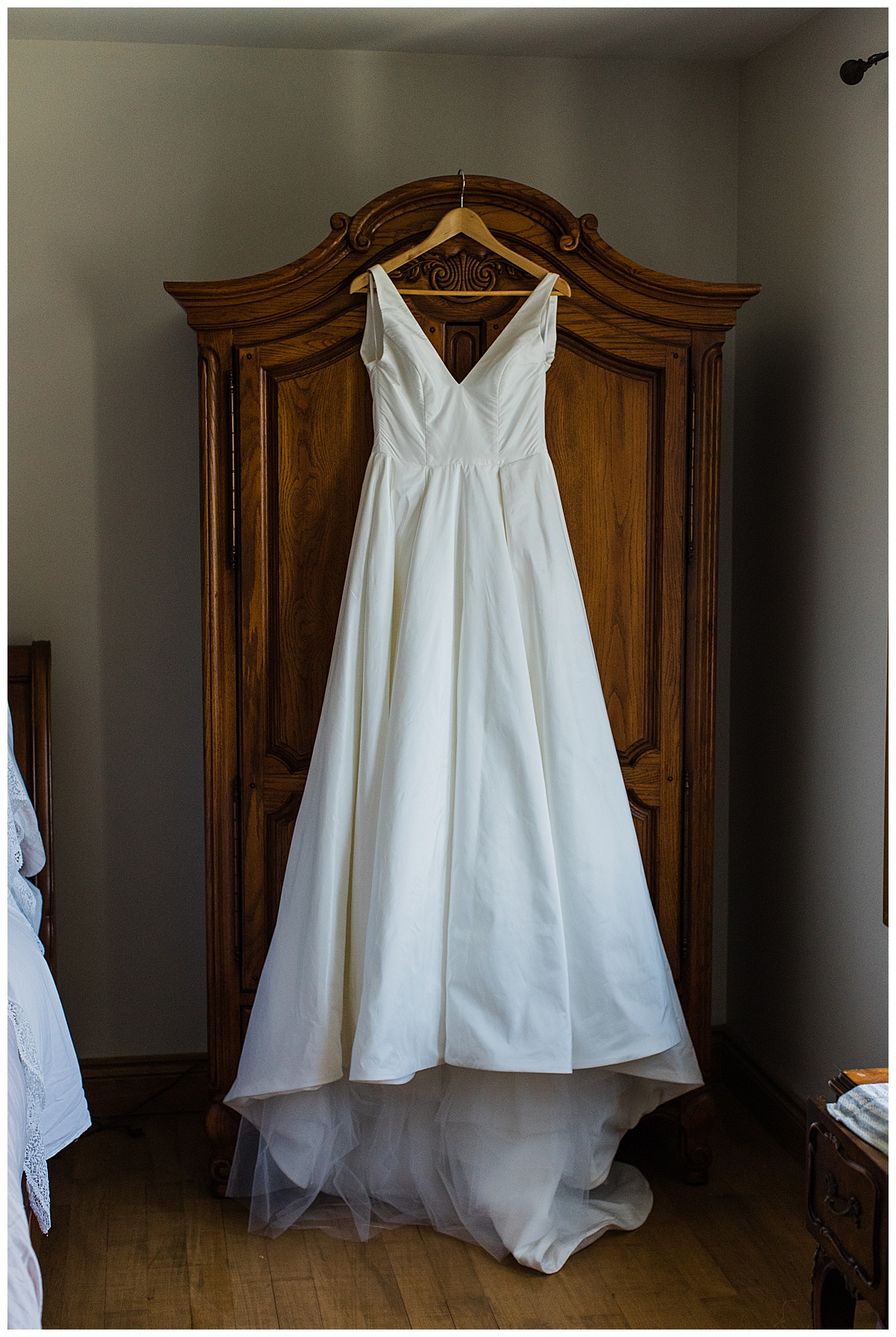 Wedding gown hanging on amour dresser  Ontario Wedding  Toronto wedding photographer  3photography