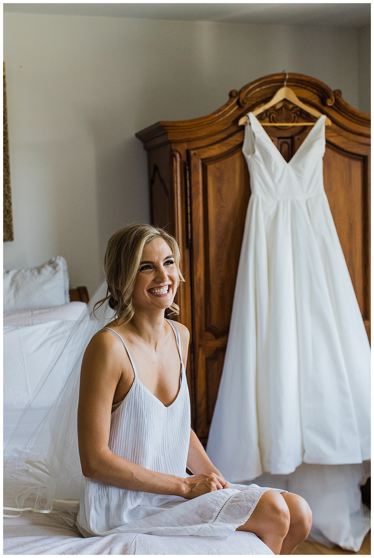 Bride sitting on bed smiling big with gown hanging on amour behind her| Georgetown, Ontario wedding|  Toronto wedding photographer| 3photography