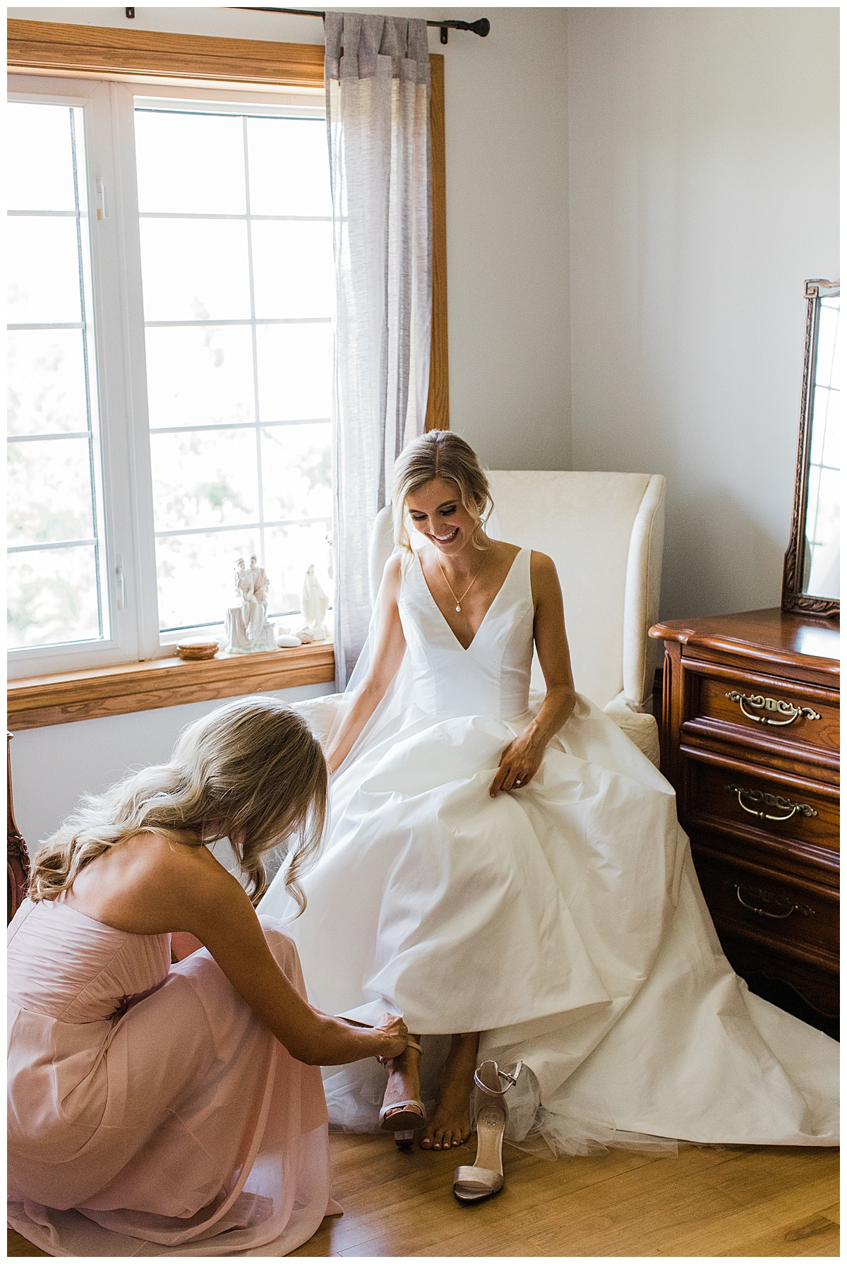 Bride sitting in chair by window while bridesmaid helps her put her bridal heels on| Georgetown, Ontario wedding| Toronto wedding photographer| 3photography