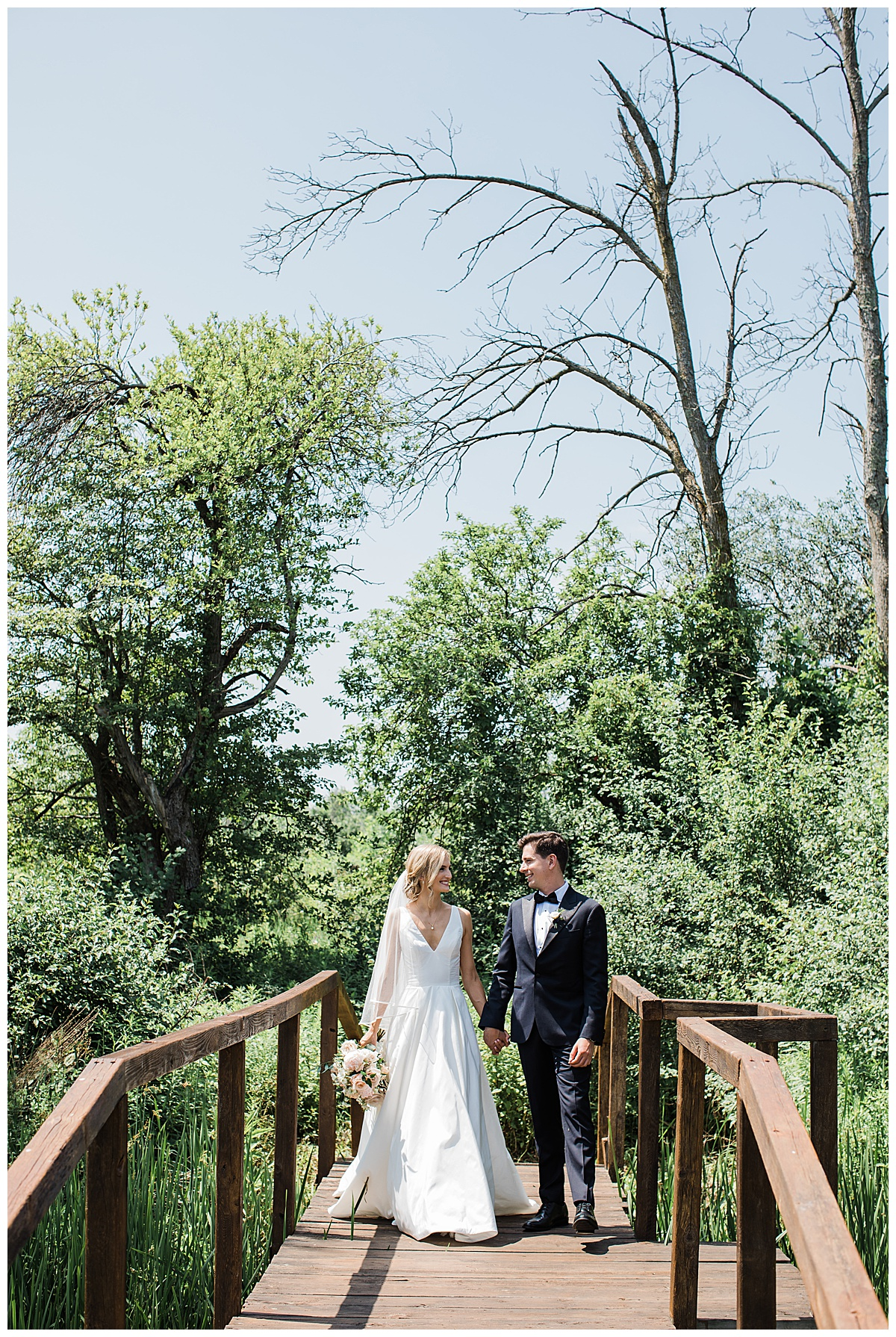 Bride and groom walking toward camera across bridge surrounded by trees  Toronto wedding photographer  3photography