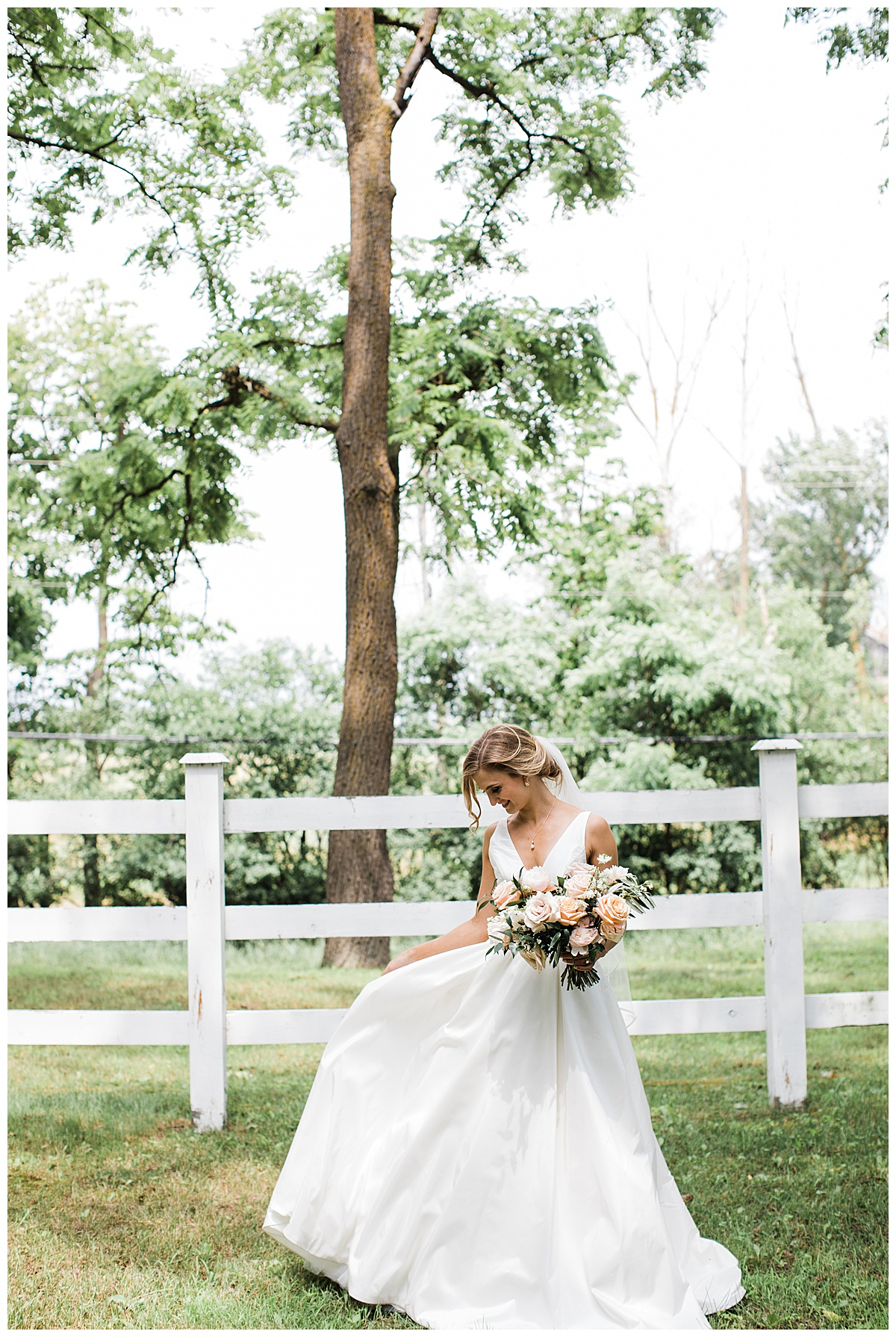 Bride under tree in front of white fence holding her gown up  Georgetown, Ontario wedding  Toronto wedding photographer  3photography