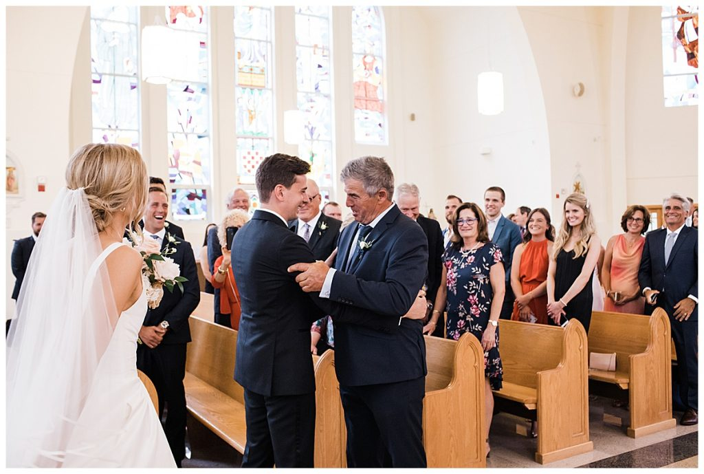 Groom and bride's father embrace each other at alter  Ontario wedding  Toronto wedding photographer  3photography