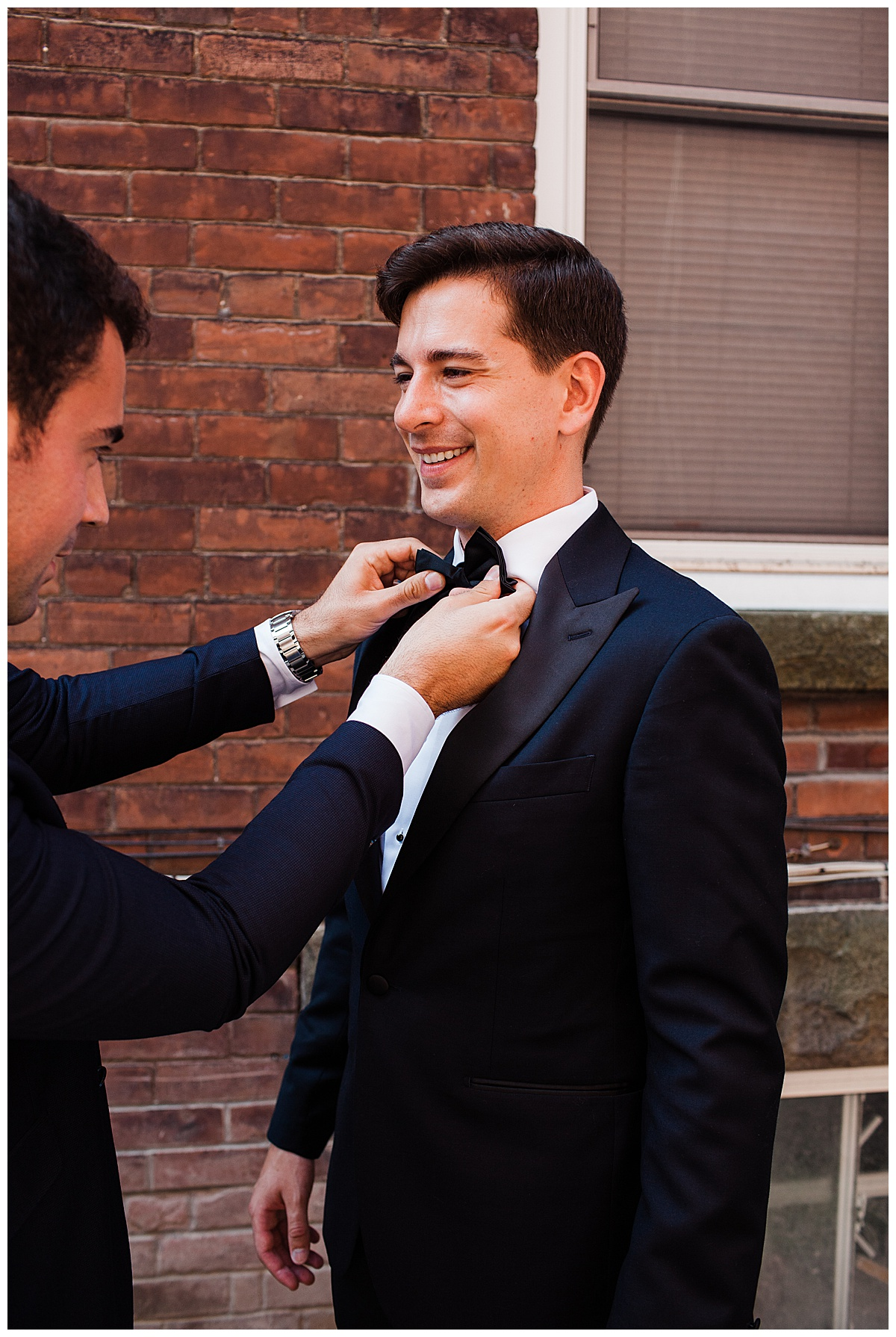 Groom smiling while his bowtie is adjusted for Ontario wedding  Toronto wedding photographer  3photography