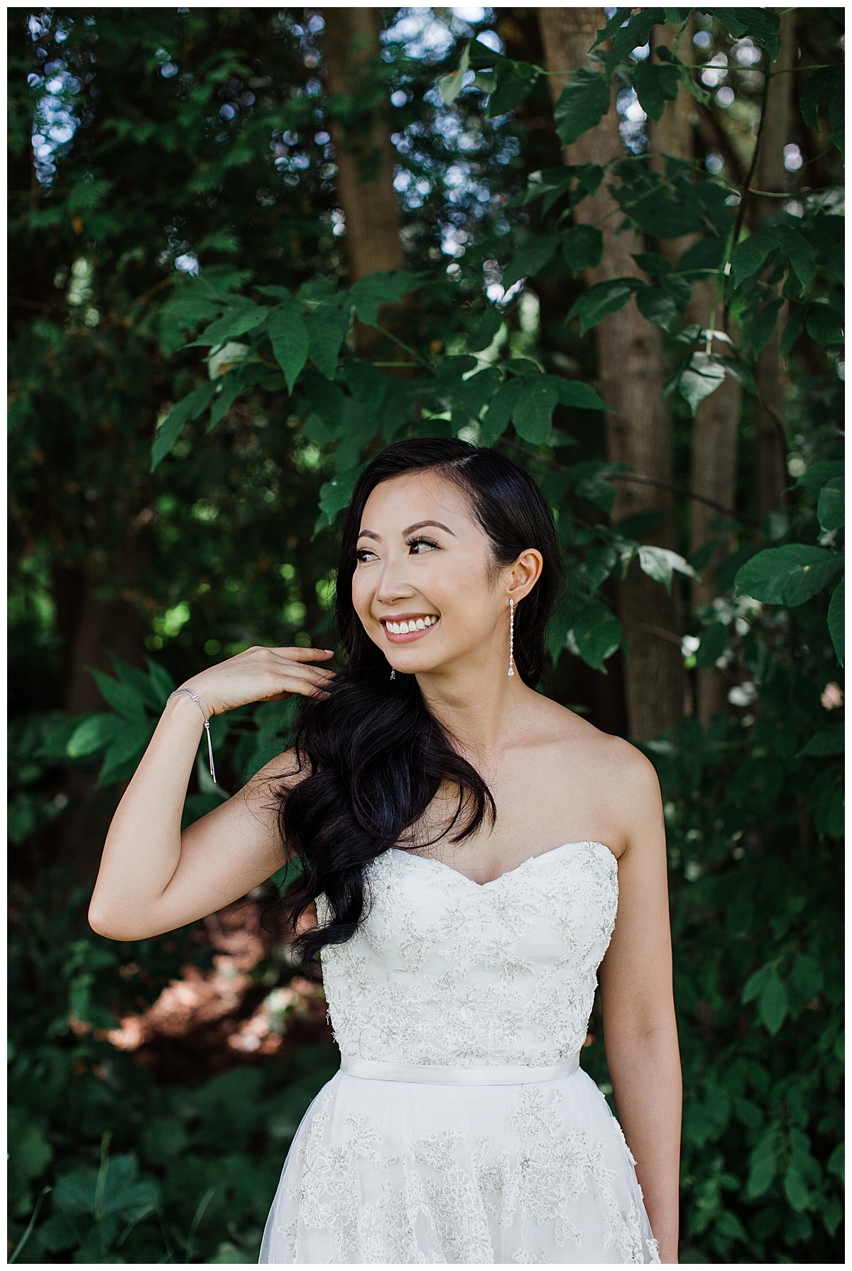 Bride smiling and looking to the side while sweeping hair over her shoulder| outdoor bridal portrait| Bride under tree| asian bride| sweetheart neckline gown| Toronto photographer| 3photography