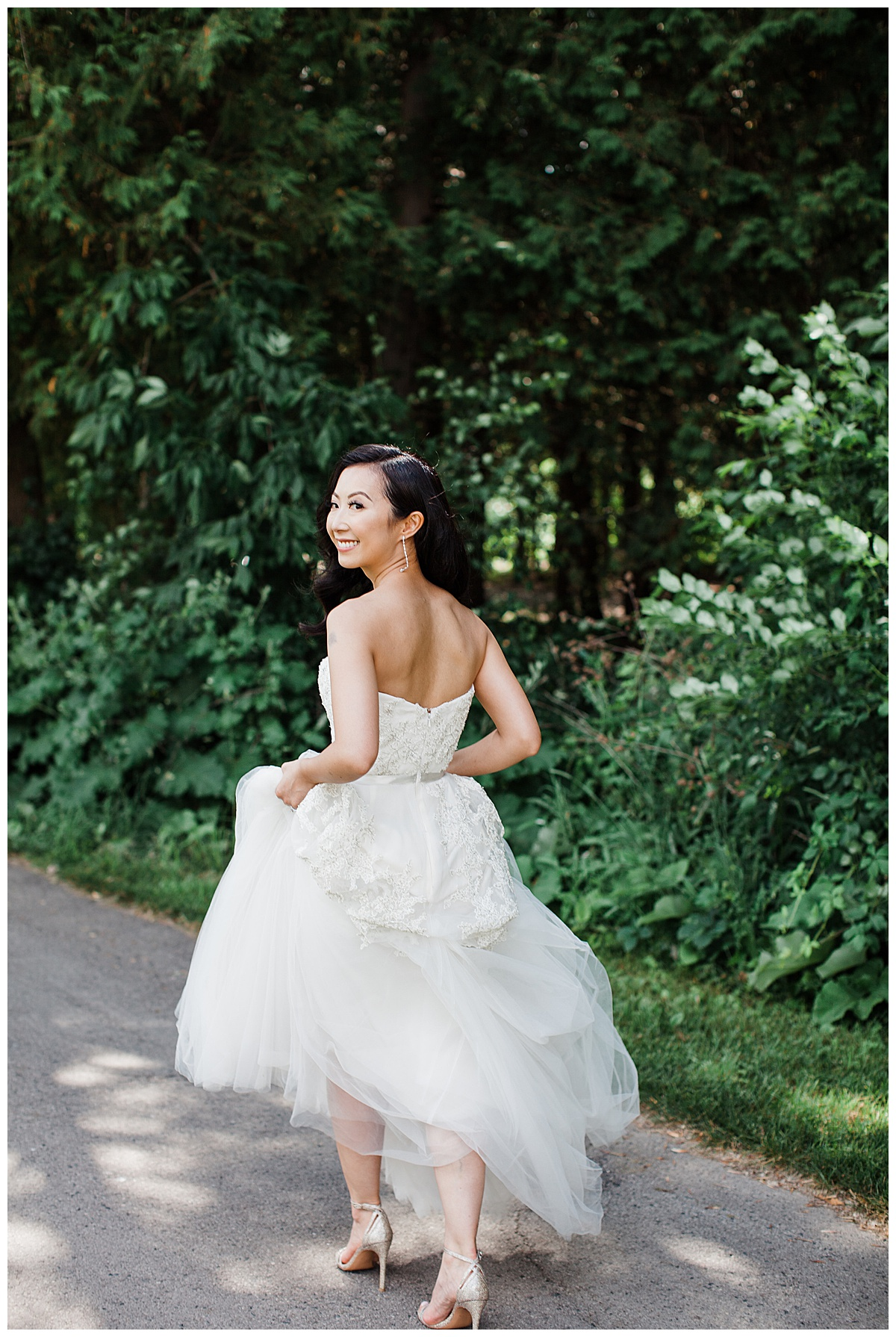 Bride holding dress up while walking and looking over her shoulder outside| outdoor bridal portrait| outdoor wedding| winery wedding| Toronto photographer| 3photography