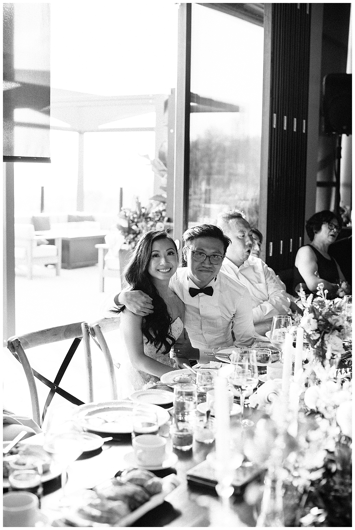 Black and white of bride and groom sitting at wedding reception table smiling| winery wedding| 3photography